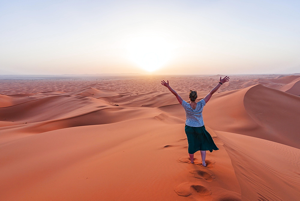 Female hiker is stretching arms in the air, red sand dune in the desert, sunset, Erg Chebbi, Merzouga, Sahara, Morocco, Africa