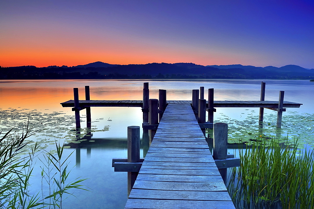 Wooden pier during dawn at Pfäffikersee, Pfäffikon, Canton of Zurich, Switzerland, Europe