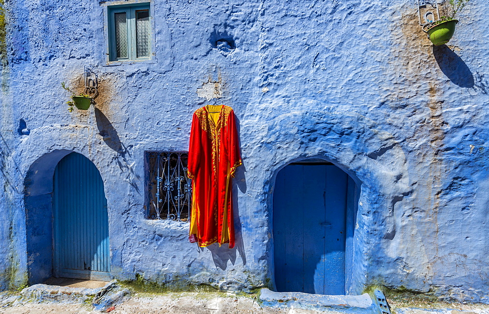 House facade, red dress hangs on blue painted house, medina of Chefchaouen, Chaouen, Tangier-Tétouan, Morocco, Africa