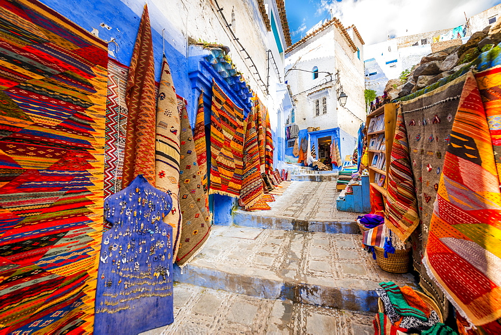 Narrow alley with carpets, carpet dealers, blue houses, medina of Chefchaouen, Chaouen, Tangier-Tétouan, Morocco, Africa