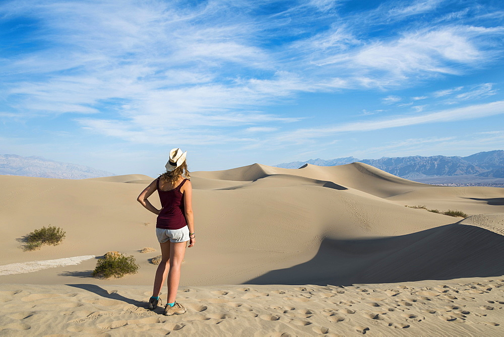 Female tourist overlooking the Mesquite Flat Sand Dunes, sand dunes, foothills of Amargosa Range Mountain Range behind, Death Valley, Death Valley National Park, California, USA, North America