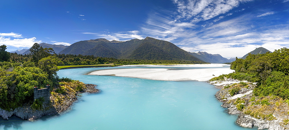 Türkiser Arawhata River, on the shore green forest, behind the summit of the Southern Alps, Mount Aspiring National Park, West Coast, South Island New Zealand