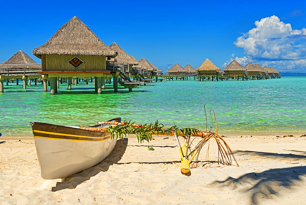 Polynesian outrigger canoe in front of pile bungalow complex, South Pacific, Bora Bora, French Polynesia, Oceania