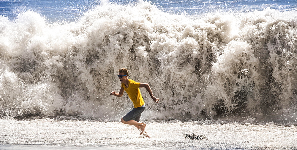 Young man with sunglasses running from a high wave, La Palma, Canary Islands, Spain, Europe