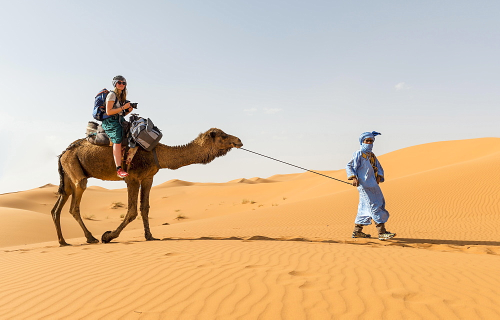 Tourist on a dromedaries with bedouin (Camelus dromedarius), sand dunes in the desert, Erg Chebbi, Merzouga, Sahara, Morocco, Africa