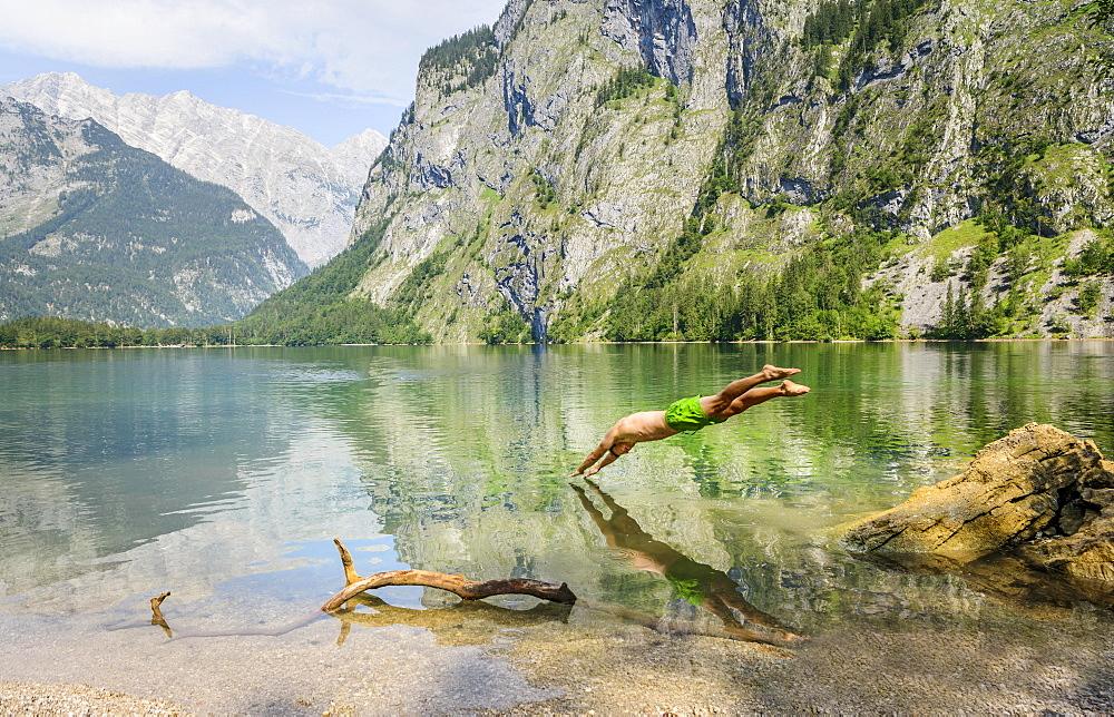 Young man jumps into Lake Obersee, swimming, mountain lake, mountain landscape, in the back Watzmann massif, Salet am Konigssee, Berchtesgaden National Park, Berchtesgadener Land, Upper Bavaria, Bavaria, Germany, Europe