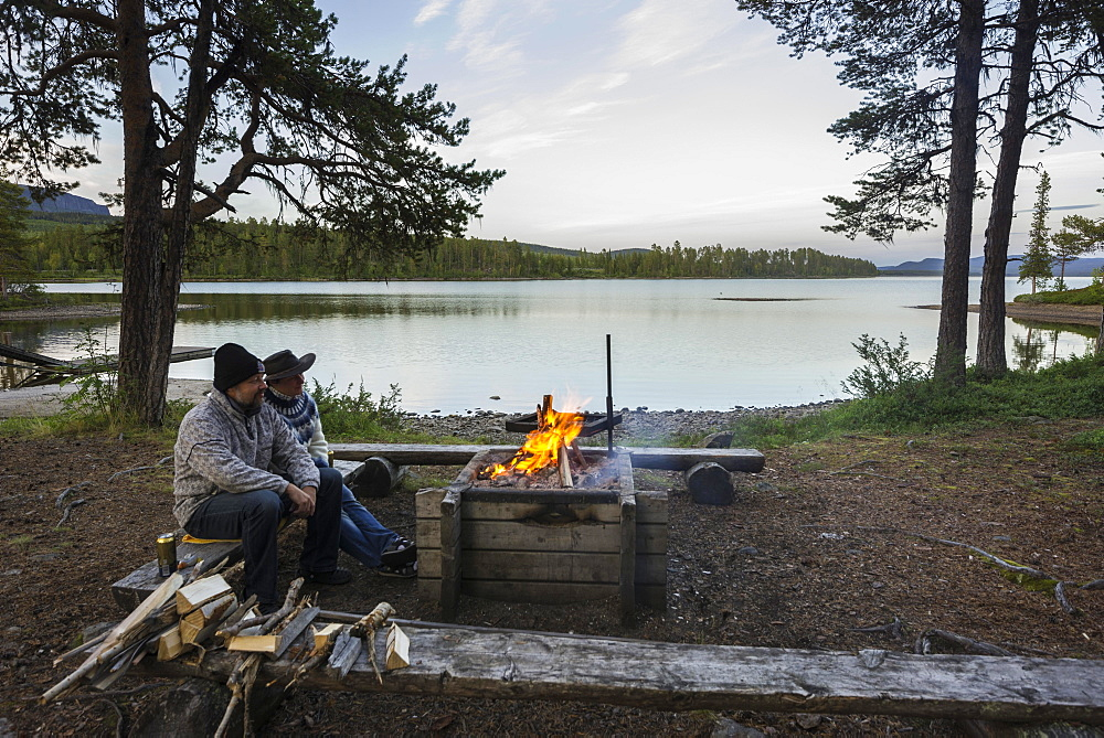Couple sitting at a campfire, campsite on Arrenjarka island, Kvikkjokk, Norrbotten County, Sweden, Europe