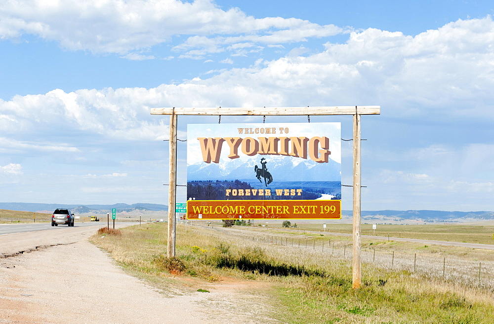 "Welcome sign on a highway, """"Welcome to Wyoming, Forever West"""", flat landscape, Wyoming, USA, North America"
