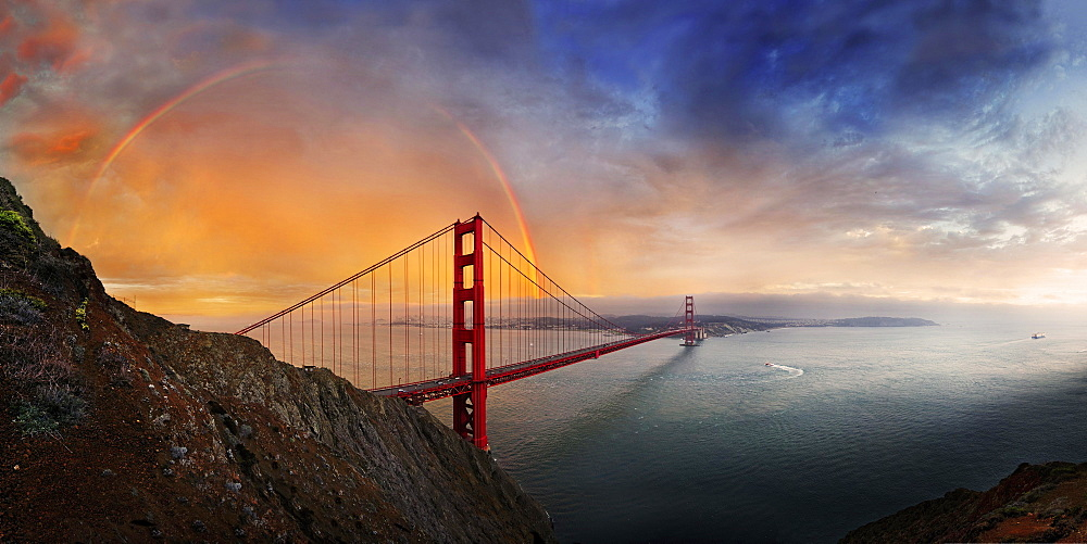 Panoramic view of the Golden Gate Bridge with a rainbow at sunset and orange-glowing storm clouds, San Francisco, California, United States, North America