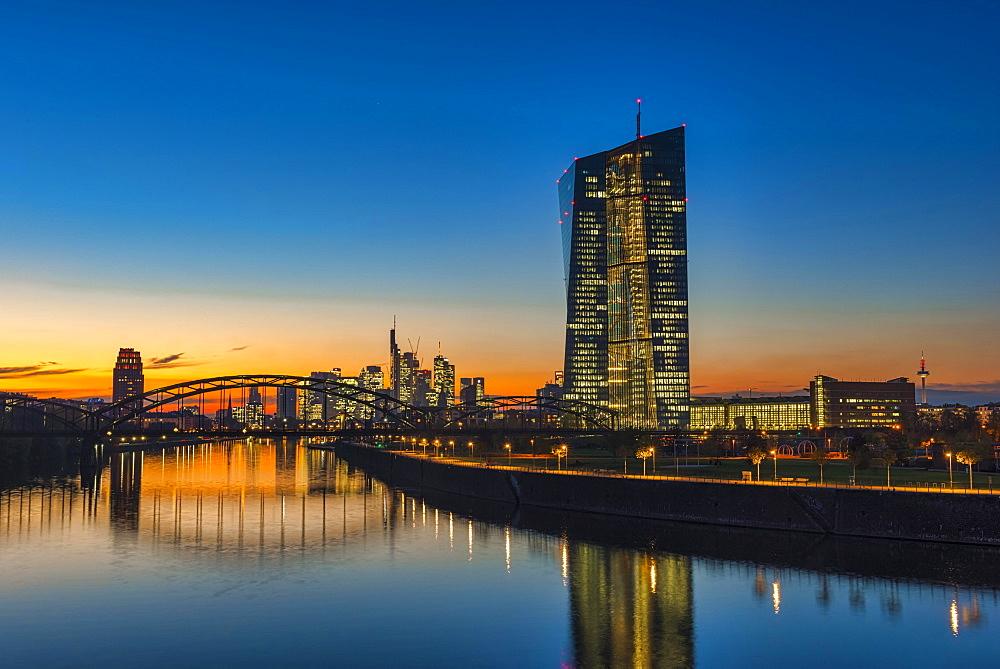 European Central Bank, ECB in front of the illuminated skyline, Osthafenbrucke, dusk, Frankfurt am Main, Hesse, Germany, Europe