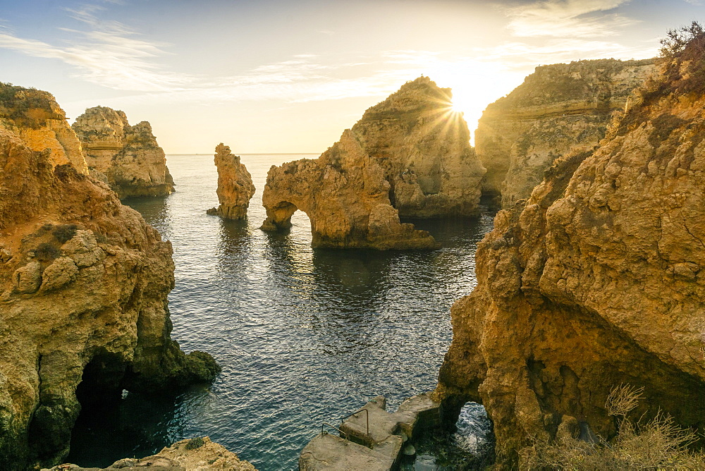 Rugged rocky coast, cliffs and arches in Ponta da Piedade at sunrise, Lagos, Algarve, Portugal, Europe