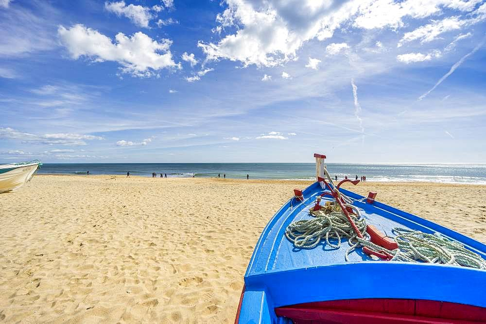 Blue, fishing boat on the sandy beach in Armacao de Pera, Algarve, Portugal, Europe