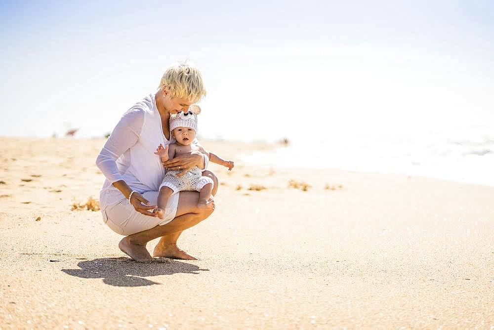 Attractive blond mother with 4 months old baby boy on the beach, Portugal, Europe