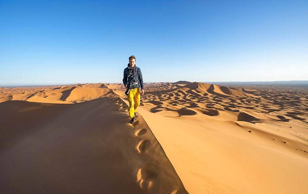 Young man running on sand dune, Erg Chebbi, Merzouga, Sahara, Morocco, Africa