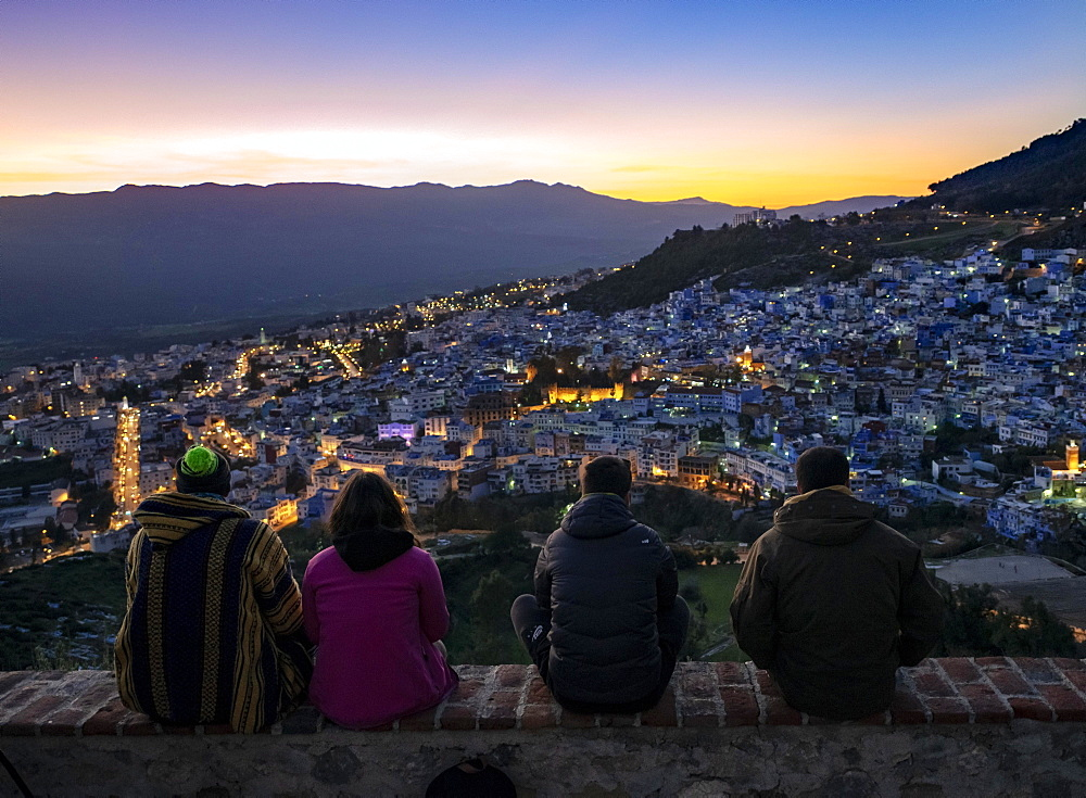People sitting on a wall overlooking city Chefchauoen, sunset, Chaouen, reef mountains, Tangier-Tetouan, Morocco, Africa