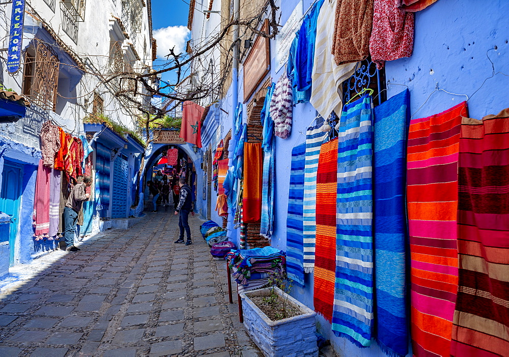 Colourful fabrics on a blue house wall, narrow alley, medina of Chefchaouen, Chaouen, Tanger-Tetouan, Morocco, Africa