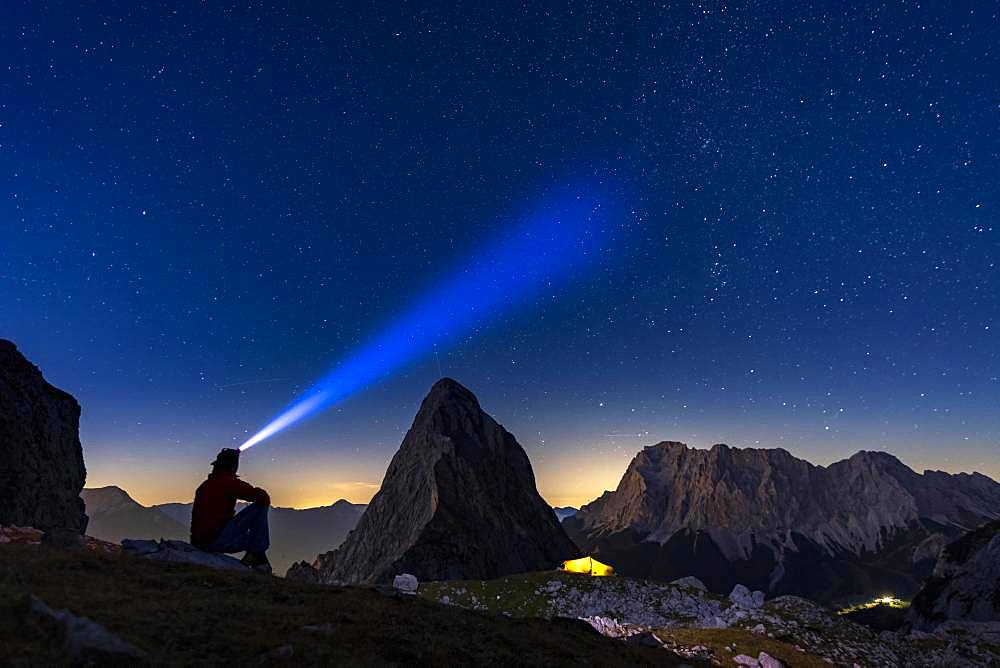 Summit of the Sonnenspitze with mountaineer and tent as well as Zugspitze in the background with blue hour and starry sky, Ehrwald, Ausserfern, Tyrol, Austria, Europe