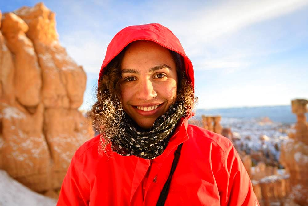 Portrait of a pretty young woman in winter clothes in front of rock needles, Winter, Rim Trail, Bryce Canyon National Park, Utah, USA, North America