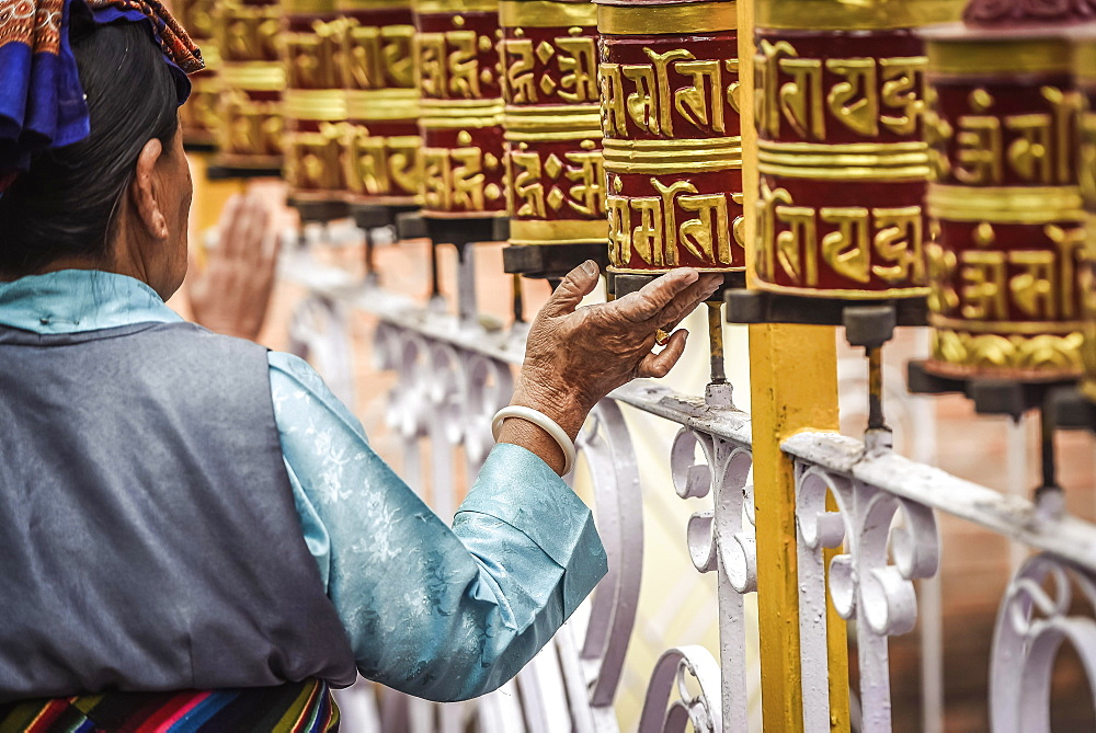 Woman turns on prayer wheels, temple, Pokhara, Nepal, Asia