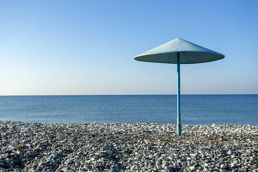Blue umbrella on the pebble beach, Cyprus, Europe