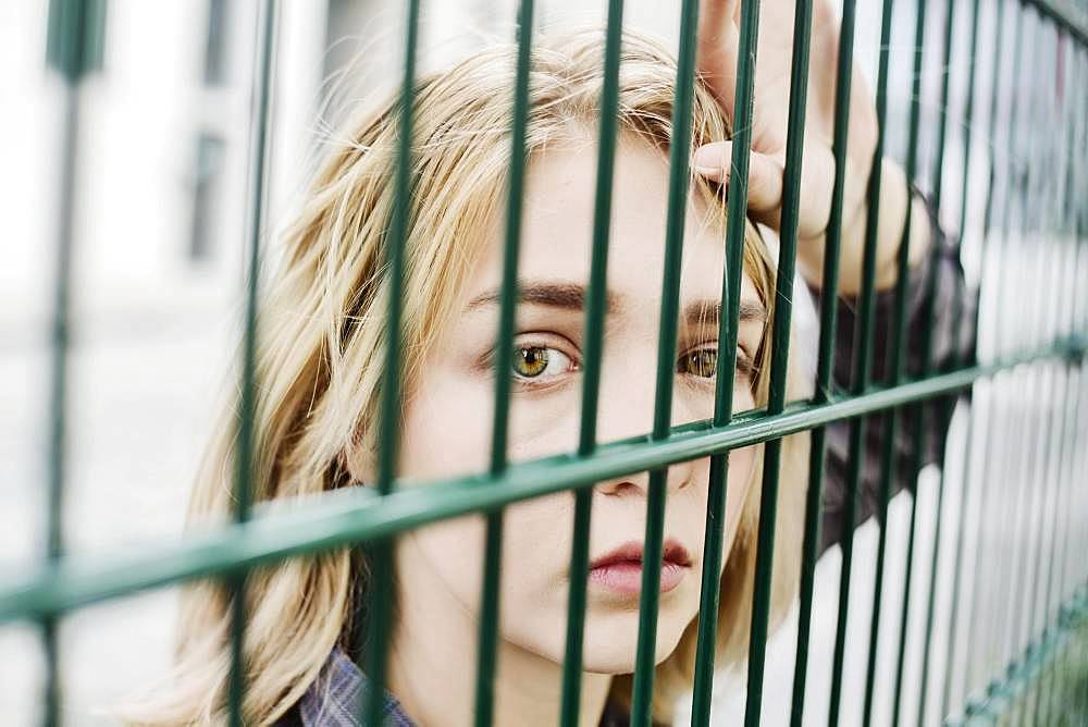 Young blonde woman, teenager looking thoughtfully through a grid, North Rhine-Westphalia, Germany, Europe