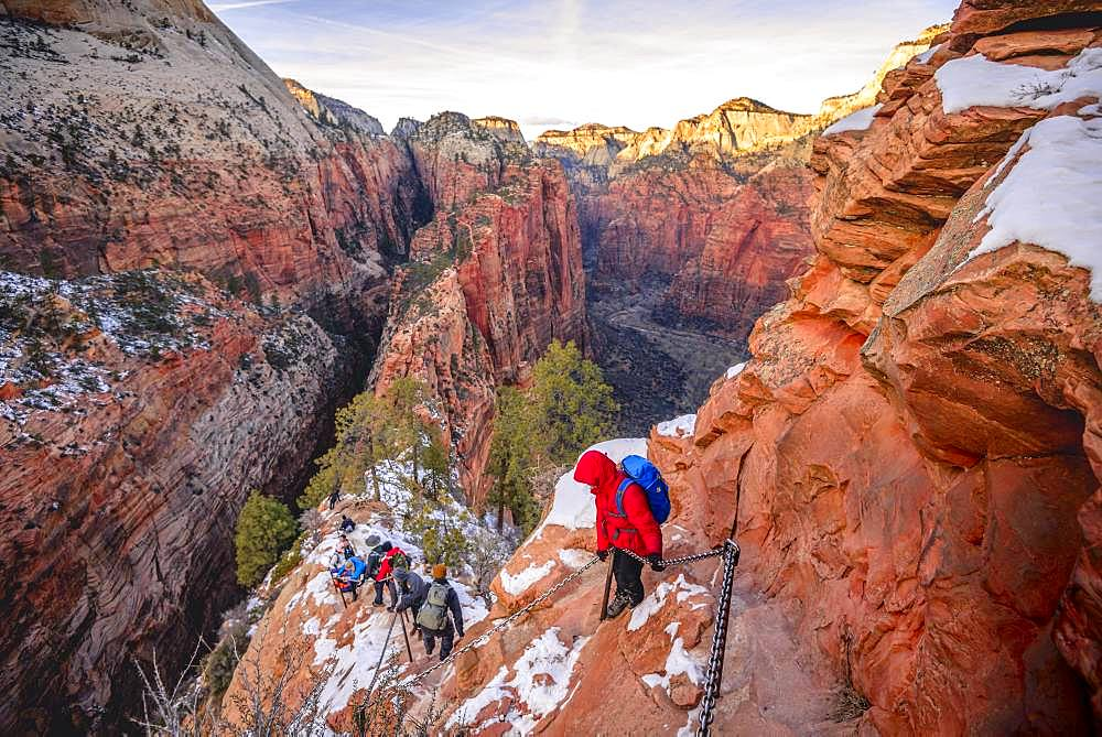 Young woman hikes on the via ferrata descending from Angels Landing, Angels Landing Trail, in winter, Zion Canyon, Mountain Landscape, Zion National Park, Utah, USA, North America
