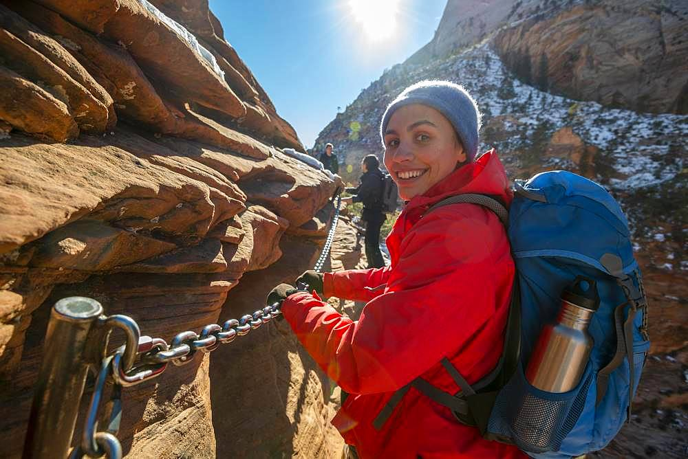 Young woman hiking on the via ferrata of the Angels Landing Trail, in winter, Zion Canyon, mountain landscape, Zion National Park, Utah, USA, North America
