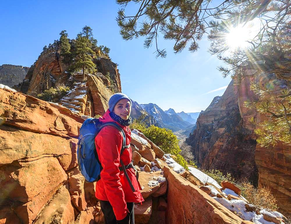 Young woman hiking on the via ferrata to Angels Landing, Angels Landing Trail, in winter, Zion Canyon, mountain landscape, Zion National Park, Utah, USA, North America