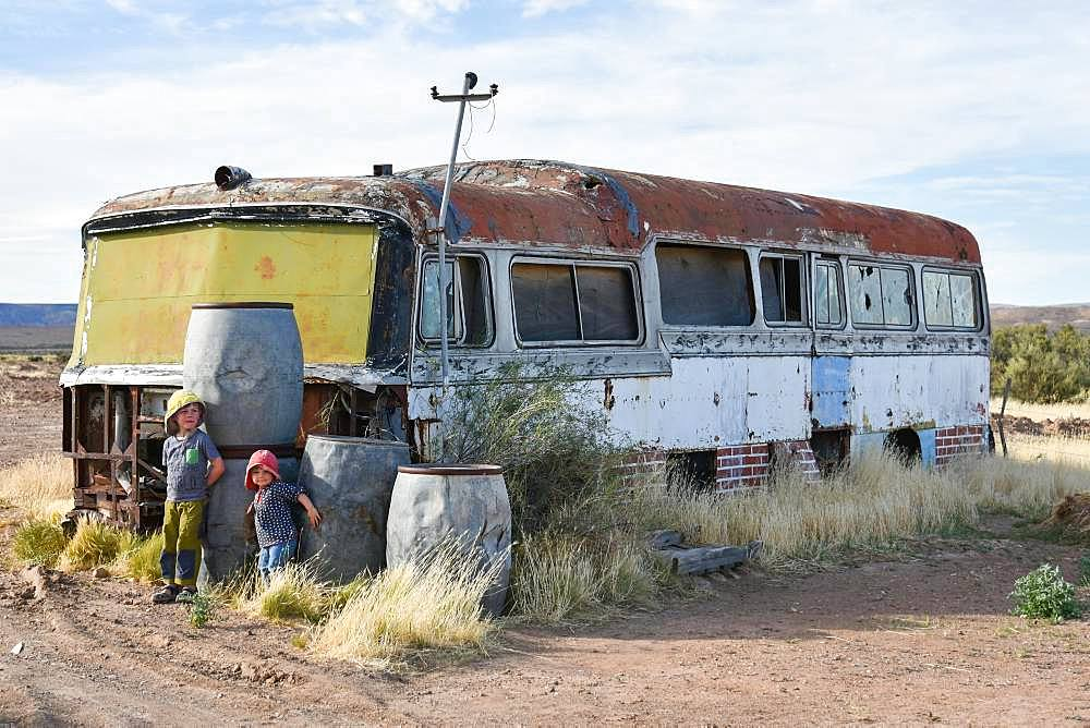 Boy and girl play at car wreck of an old bus, Bosques Petrificados de Jaramillo National Park, Patagonia, Argentina, South America