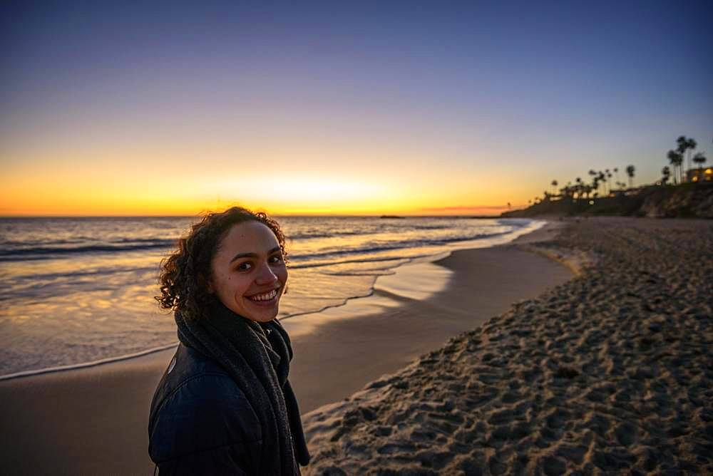 Young woman on the beach at sunset, Laguna Beach, Orange County, California, USA, North America