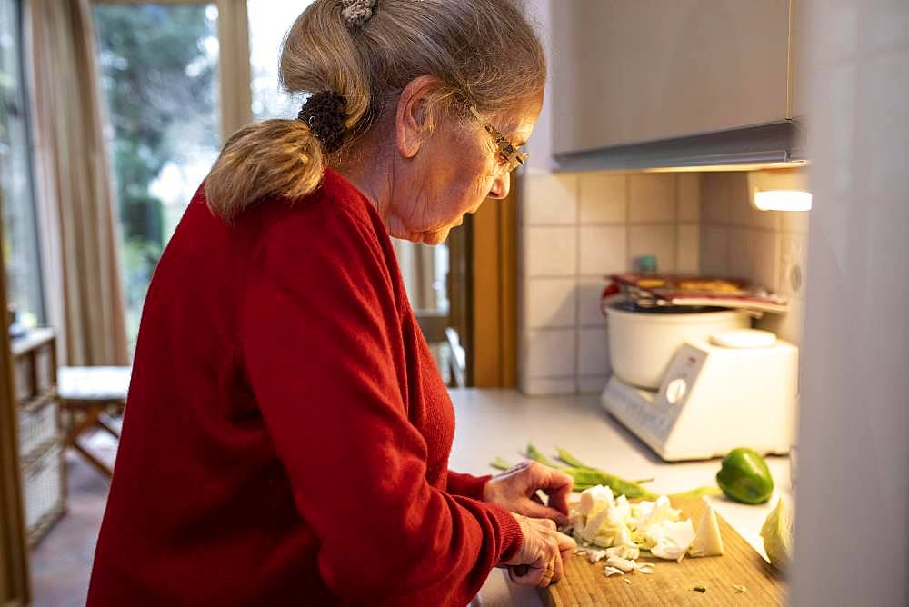 Senior cuts vegetables in the kitchen, Germany, Europe