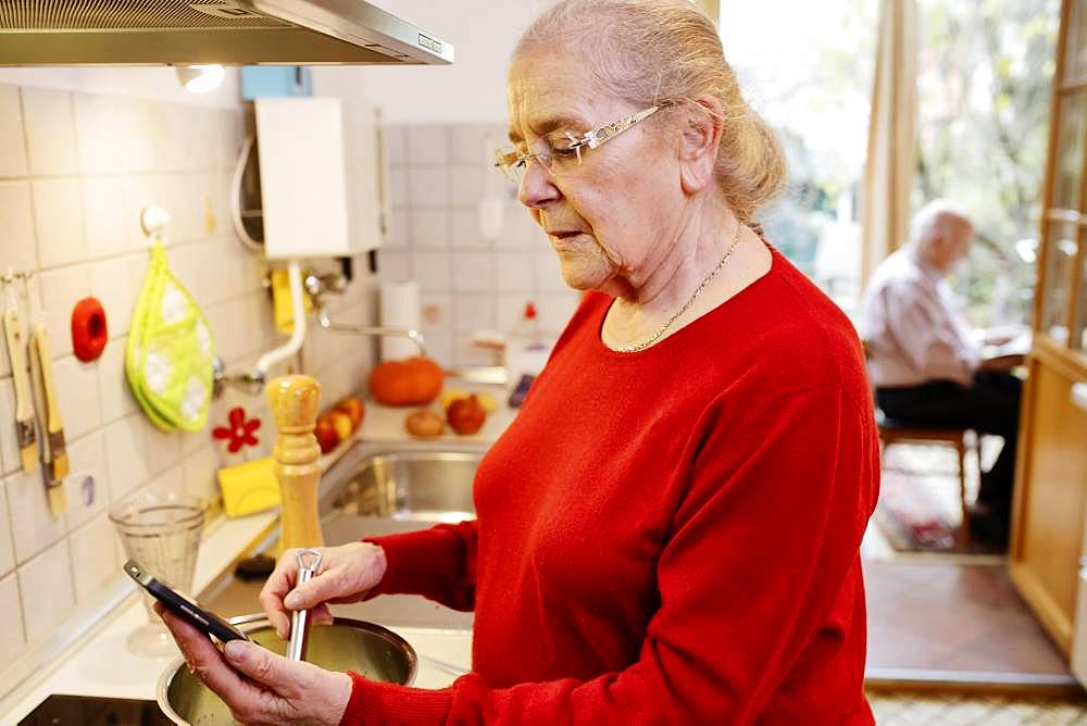 Senior citizen cooks a recipe from the Internet, holds mobile phone in her hand, North Rhine-Westphalia, Germany, Europe
