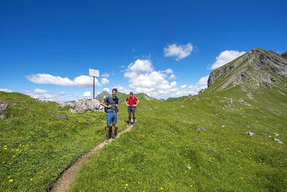 Two hikers on hiking trail Jubilaeumsweg at the Kirchdachsattel, sign state border, Allgaeuer Alps, Allgaeu, Bavaria, Germany, Europe