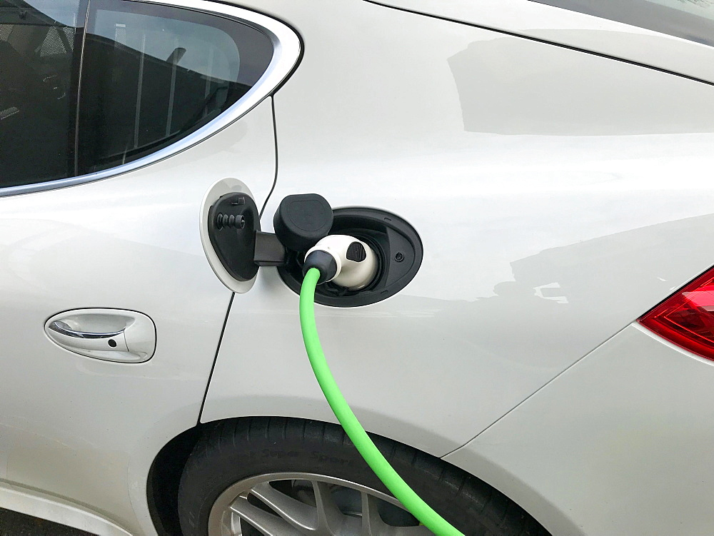 Charging plug on electric car, car being charged at charging station, Germany, Europe