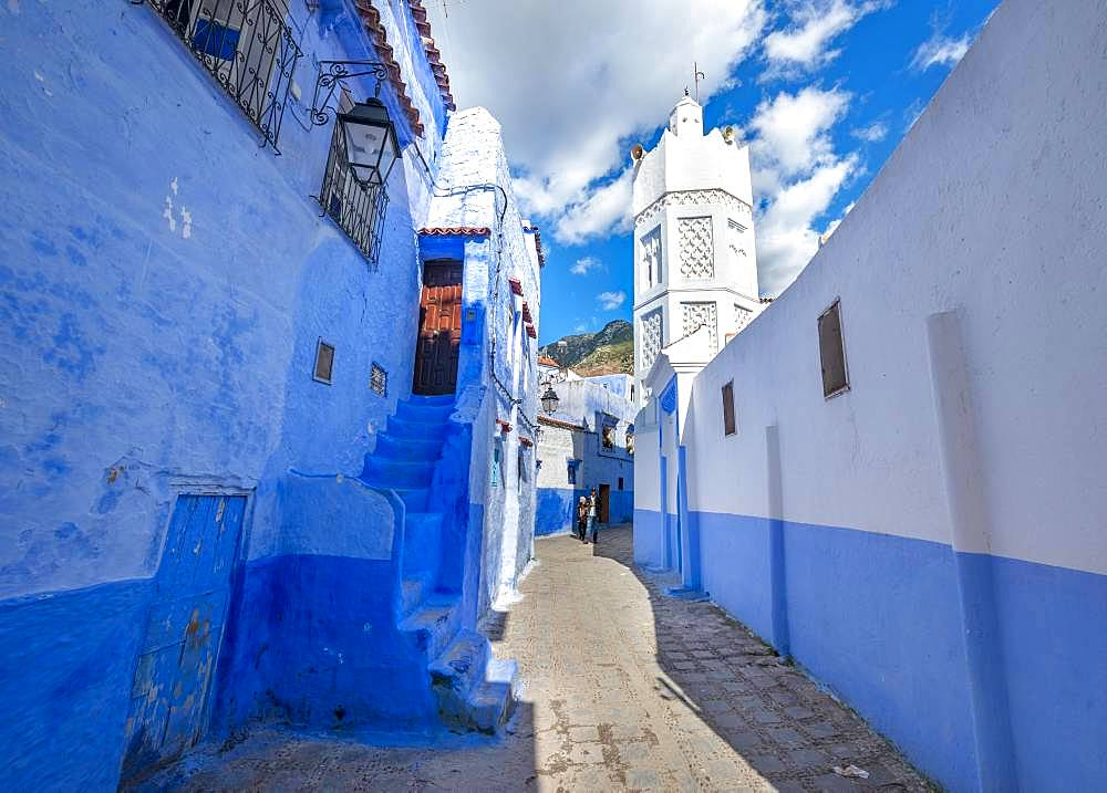 Minaret of a mosque, narrow lane between blue houses, Medina of Chefchaouen, Chaouen, Tanger-Tetouan, Morocco, Africa