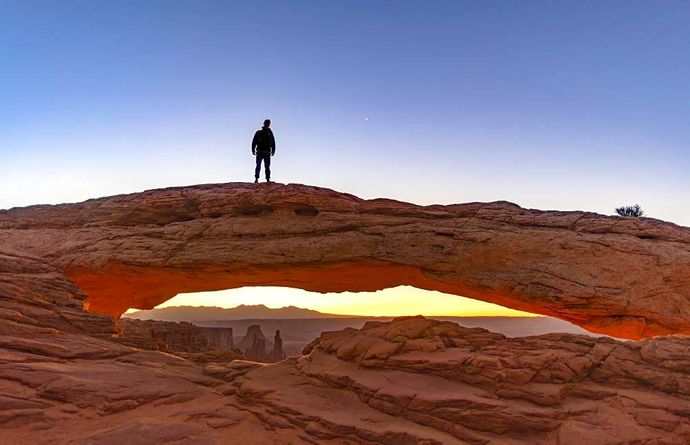 Young man standing on rock arch, Mesa Arch, sunrise, Grand View Point Road, Island in the Sky, Canyonlands National Park, Moab, Utah, USA, North America
