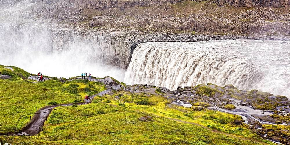 Hikers at the edge of the Dettifoss waterfall with falling water masses, North Iceland, Iceland, Europe