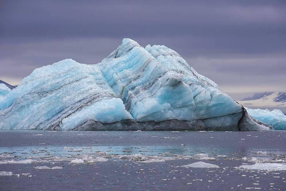 Floating chunk of ice before a huge glacier in Hornsund, Arctic, Svalbard, Norway, Europe