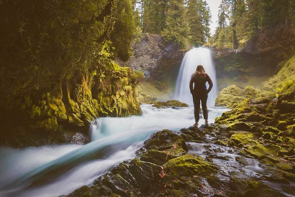 Woman in front of a waterfall, Sahalie Falls, Oregon, USA, North America