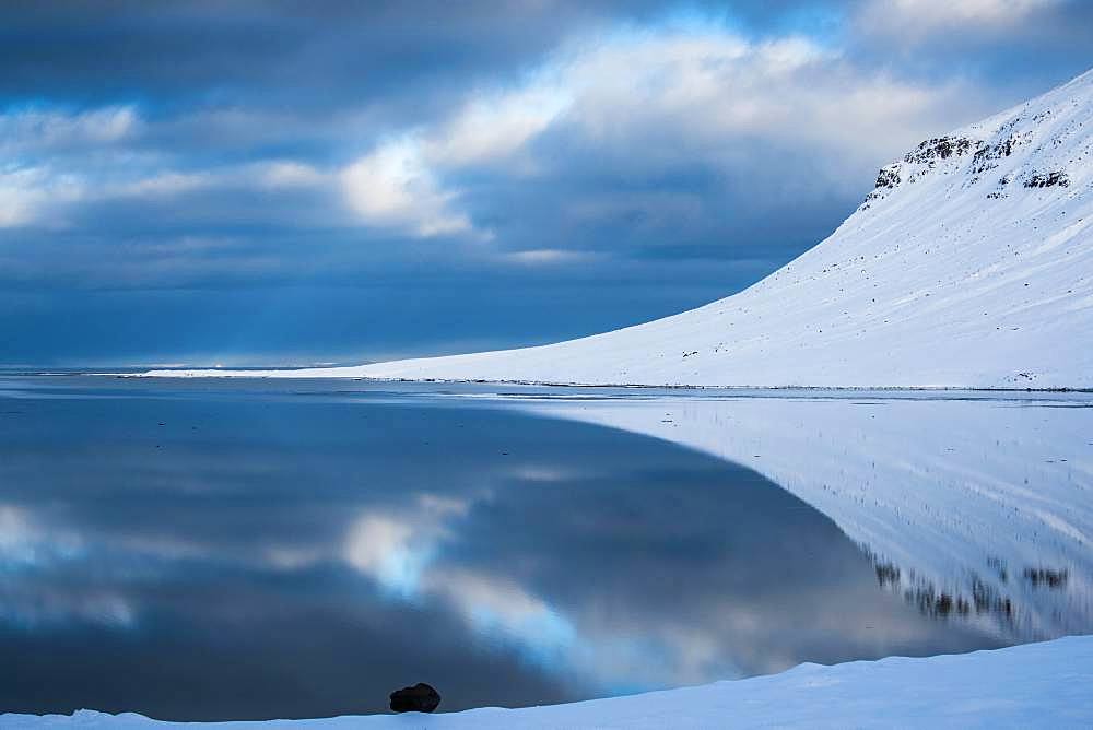 Snow-covered coastal landscape with water reflection, north coast of the peninsula Snaefellsnes, Grundarfjoerdur, Iceland, Europe