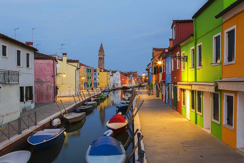 Moored boats on canal lined with colourful houses, behind San Martino church at dusk, Burano Island, Venetian Lagoon, Venice, Veneto, Italy, Europe