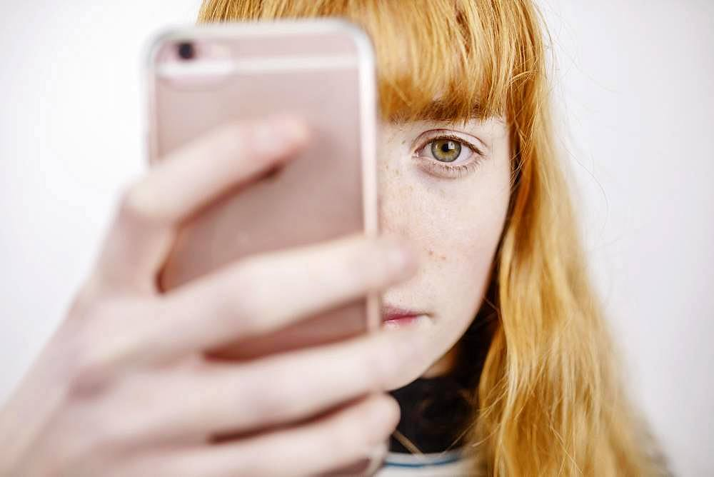 Girl, teenager, with smartphone, looks thoughtful, studio shot, Germany, Europe