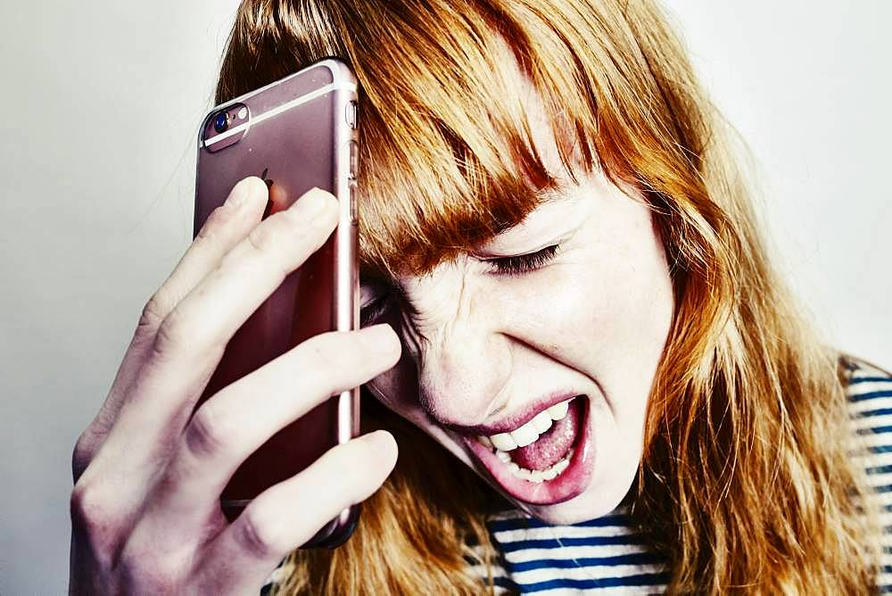 Girl, teenager, red-haired, holding her head in despair screaming smartphone, studio shot, Germany, Europe