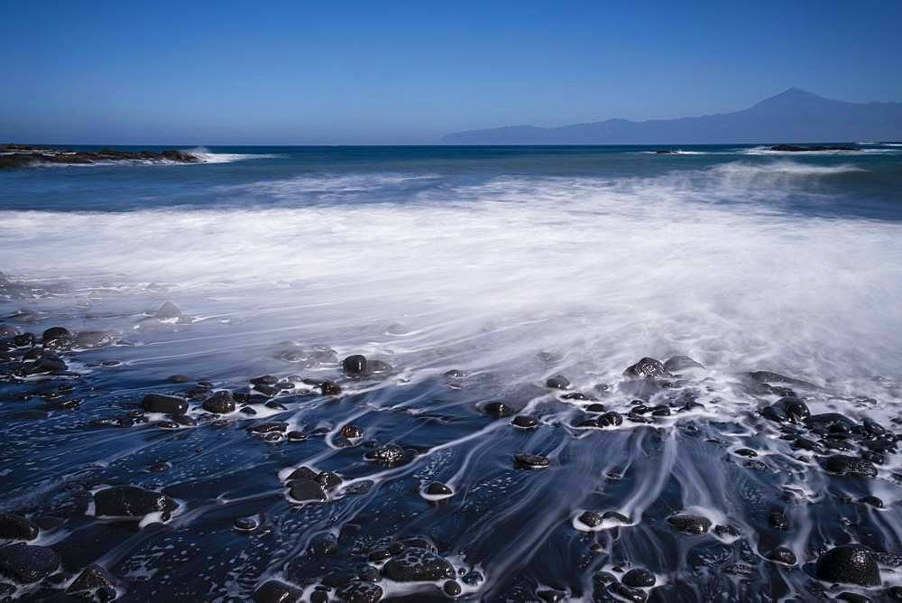 Black pebble beach with wave hem, time exposure, view to Teide on Tenerife, Playa de Caleta, La Gomera, Canary Islands, Spain, Europe