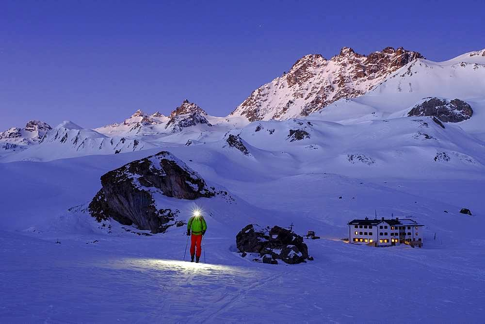 Ski tourer with headlamp in front of Heidelberger Huette, dawn, Silvretta, Graubuenden, Switzerland, Europe