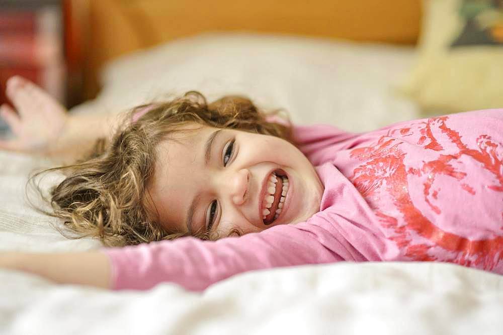 Girl, 3 years old, portrait, lies relaxed and laughing in bed, Germany, Europe