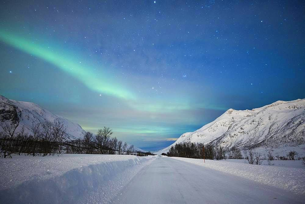 Northern lights at the snow-covered Kattfjordpass, Tromso, Norway, Europe