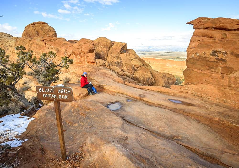 Tourist, young woman resting at Black Arch Overlook, viewpoint, sandstone cliffs, Devil's Garden Trail, Arches National Park, Utah, USA, North America