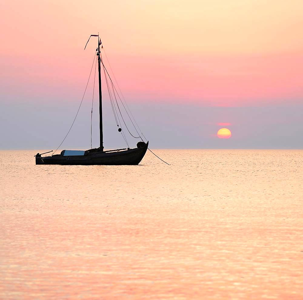 Sunset at the Baltic Sea, traditional sailing boat anchored, West beach, Baltic seaside resort Wustrow, Fischland-Darss-Zingst, Mecklenburg-Western Pomerania, Germany, Europe