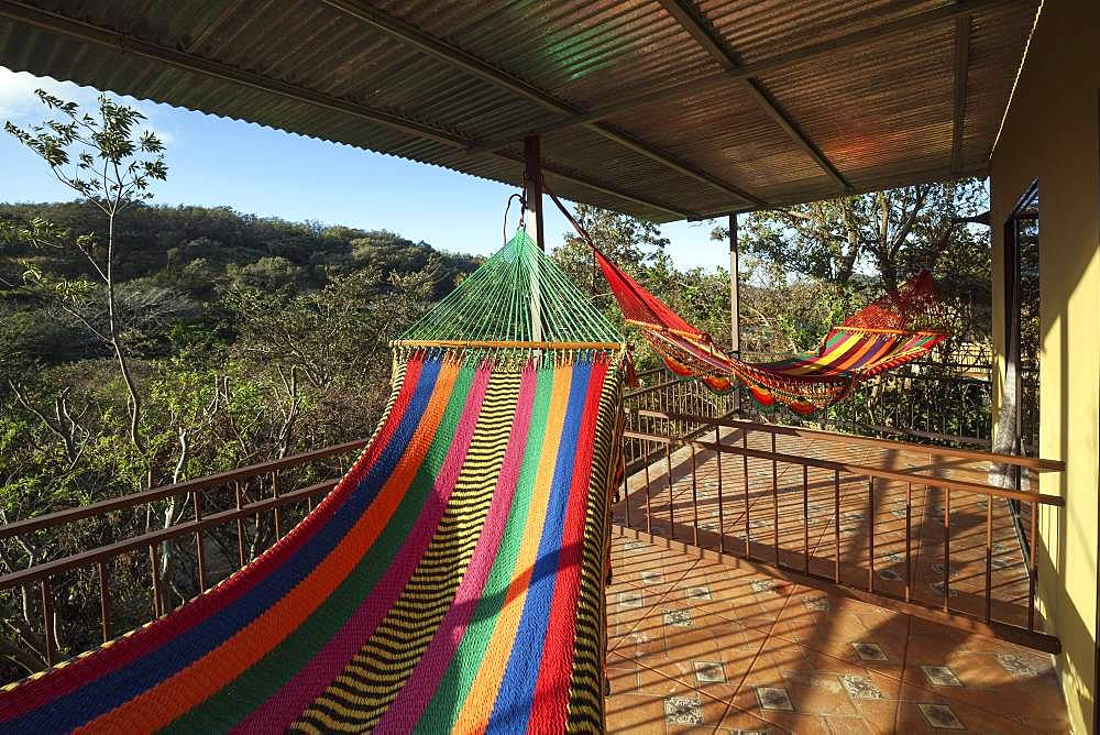 Colourful hammocks on the terrace, Rinconcito Lodge at Rincon de la Vieja National Park, near Liberia, Guanacaste Province, Costa Rica, Central America